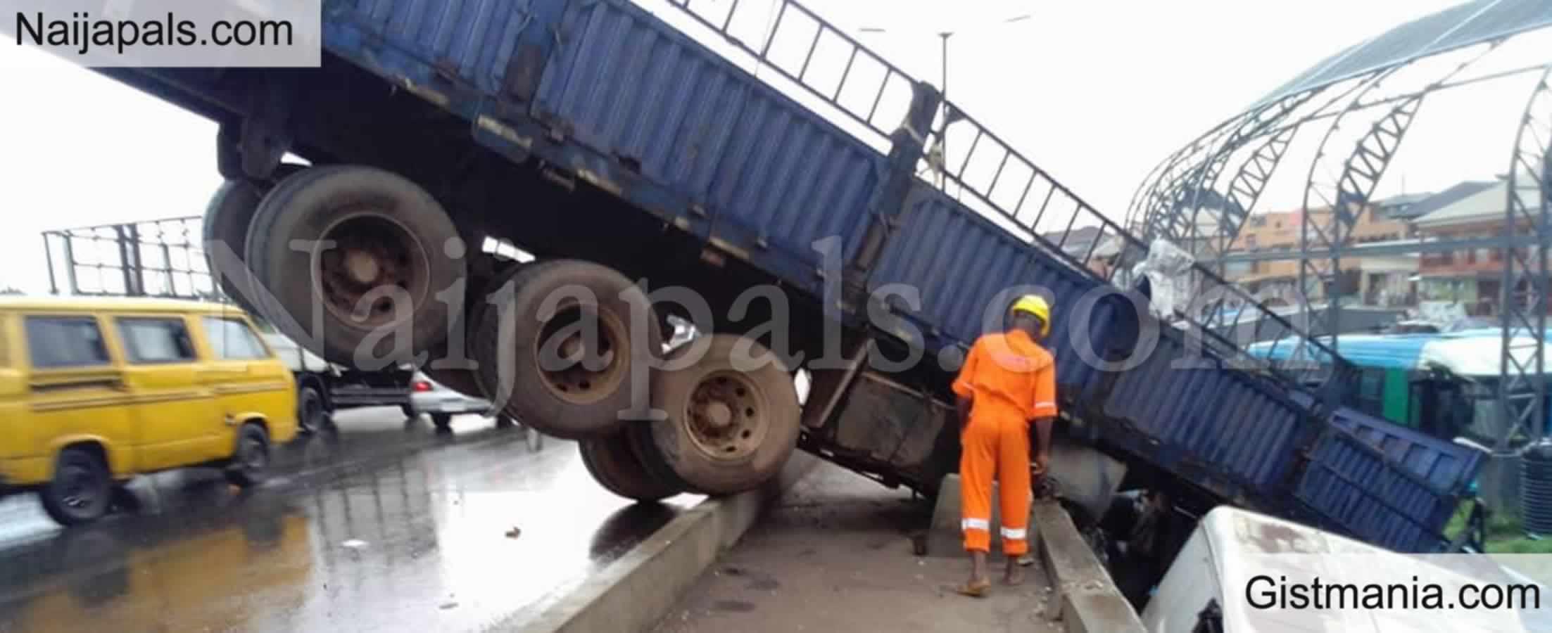 <img alt='.' class='lazyload' data-src='https://img.gistmania.com/emot/shocked.gif' /> <b>Tension As Many Escape Death After Truck Falls Off Oshodi Bridge In Lagos</b>